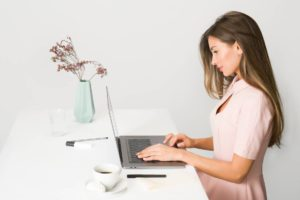 woman in pink dress using laptop computer